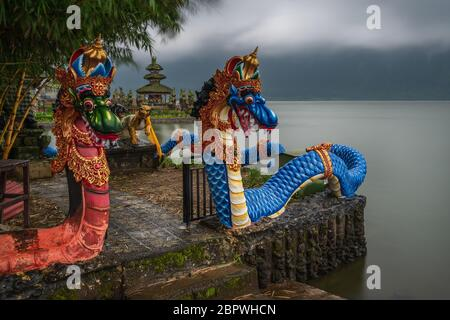 Bedugul, Lake Beratan, Tabanan, Bali, Indonesia - March 21, 2019 : The mystical dragons at Ulun Danau Beratan temple on a cloudy and rainy morning - Stock Photo
