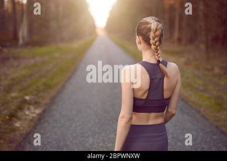 Sporty healthy young woman walking at sunrise along a rural road through a dense forest towards the glow of the sun at the end between the trees in a - Stock Photo