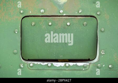 Close up of old aircraft green painted aluminum hatch with rivets.