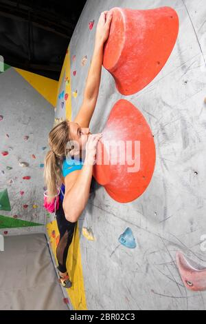 Rock climber woman hanging on a bouldering climbing wall, inside on colored hooks. - Stock Photo