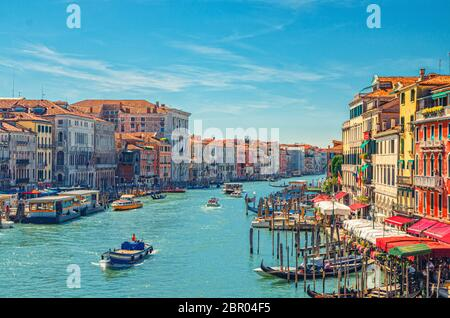 Venice cityscape with Grand Canal waterway. View from Rialto Bridge. Gondolas, boats, vaporettos docked and sailing Canal Grande. Venetian architecture colorful buildings. Veneto Region, Italy.