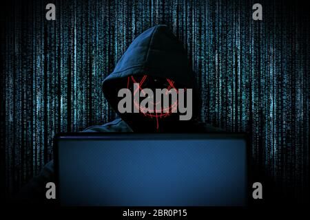 hacker with red glowing mask behind notebook laptop in front of blue source binary code background internet cyber hack attack computer concept