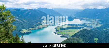 Wide panoramic view of Lake Wolfgangsee, mountains and hills from Zwolferhorn mountain above Sankt Gilgen in the Salzkammergut region, Austria - Stock Photo