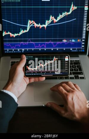 investment stockbroker risk analysis using multiple devices.Trader analyzing trade chart graph. vertical photo. - Stock Photo
