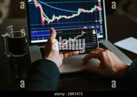 investment stockbroker stock market trading. Financial analysis using phone app and laptop. Market trading profit. - Stock Photo