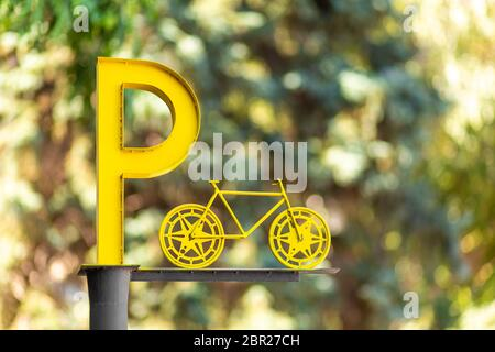 Designation of parking for bicycles. Big yellow letter P on a pillar. - Stock Photo