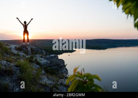 Silhouette of happy woman spreading arms and watching the mountain. Travel Lifestyle success concept adventure active vacations outdoor freedom - Stock Photo