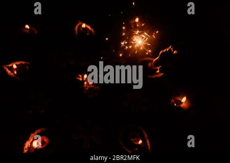 A burning Sparklers on hand over Diya-oil Lamps lit with real red flame in festival season of Diwali on black background. Removing darkness concept. S - Stock Photo