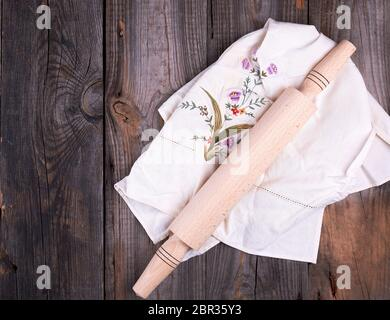 new wooden rolling pin on a textile napkin with embroidery, gray wooden background - Stock Photo