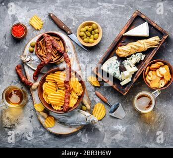 Large selection of snacks for beer. Set of cheeses, fish, chips and snacks - Stock Photo