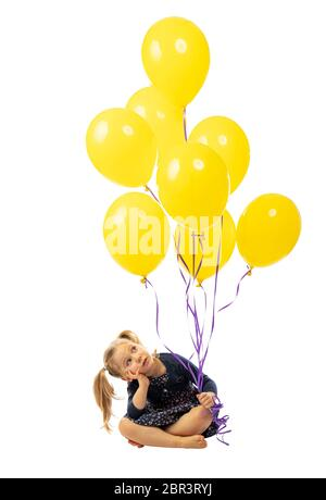 sitting little girl holding yellow balloons in her hand. isolated on white. hair with pigtails, bored expression. - Stock Photo