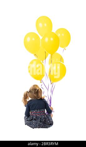 sitting little girl holding yellow balloons in her hand. isolated on white background. seen from behind. - Stock Photo