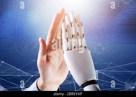 Close-up Of Robot And Man Giving High Five Against Digital Background - Stock Photo