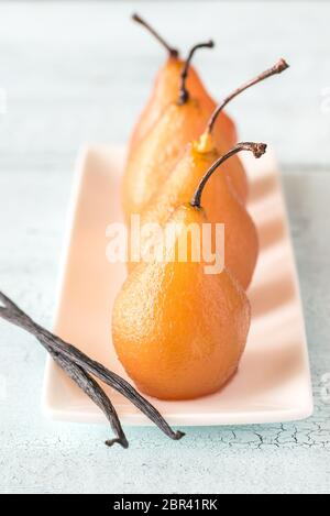 Poached pears in rose wine on the plate - Stock Photo