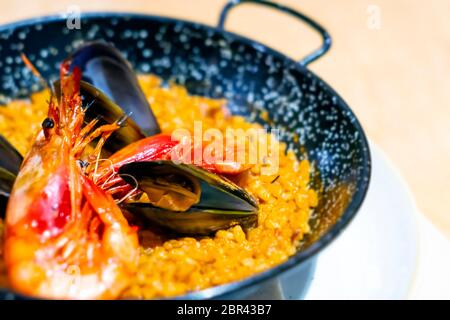 Paella with mariscos in a black pan, a typical dish of traditional Spanish cuisine based on seafood and rice. Traditional cuisine Stock Photo