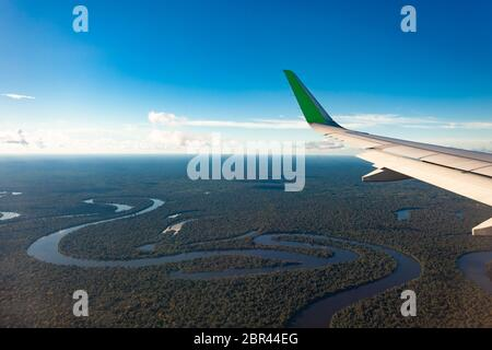 Flying over the Amazonas river, airplane wing. - Stock Photo