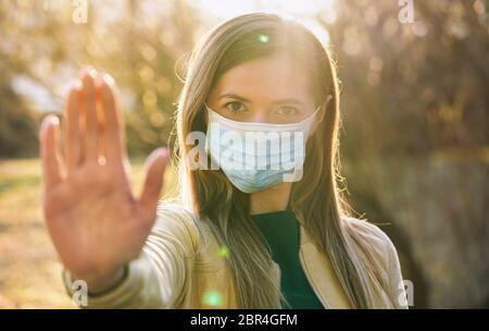 Young woman wearing blue disposable single use virus mouth nose mask, hold hand front of her as stop gesture, blurred sunset lit trees in background.