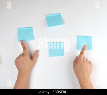 lot of blue stickers on a white background and two female hands pointing at them, conceptual background