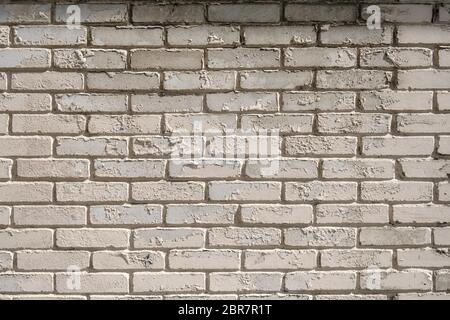 Wall of white brick with peeling off paint outdoors. Background.
