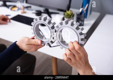 Close-up Of Two Businesspeople's Hand Connecting Gray Gears In Office