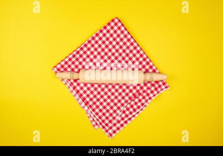 new wooden rolling pin on a red textile napkin, yellow  background, top view - Stock Photo
