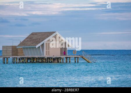 Amazing sunset sky and reflection on calm sea, Maldives beach landscape of luxury over water bungalows. Exotic scenery of summer vacation and holiday - Stock Photo