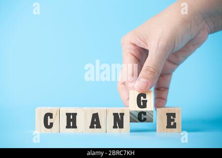 Woman hand hold wooden cube word on business blue background concept for change mindset to building organisation growth in success, chance of solution