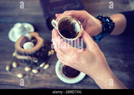 woman hold the mug and telling fortune with traditional turkish coffee cup