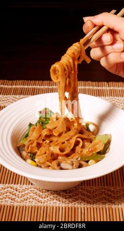 DAN DAN GLUTEN FREE NOODLES WITH CORN,  PAK CHOY, MUSHROOMS, CAPSICUM, ONION,  SPINACH - Stock Photo