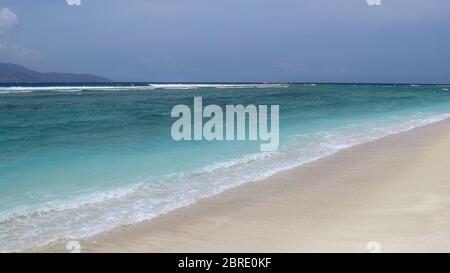 Beautiful blue ocean and tropical white sand beach on sunny summer day. Amazing sea view with azure crystal water. Scenic cloudy sky in background. To - Stock Photo