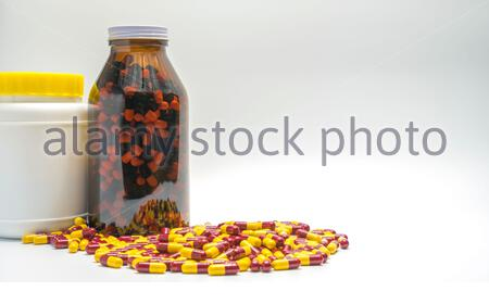 Red, yellow antibiotic capsule pills and bottles, drug resistance on white back ground with copy space - Stock Photo