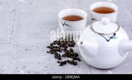 Hot tea in white teapot and cups on a sieve over bright gray cement background, closeup, copy space design concept. - Stock Photo