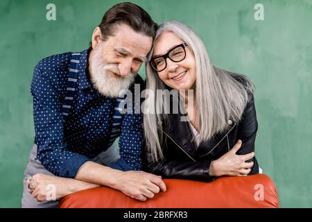 Smiling beautiful senior couple in love enjoying time together, leaning on red chair and touching foreheads, while standing in modern room in front of