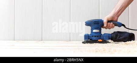 Detail of person working with an electric sander on the natural wooden floor of his house. Space for text. Work, home decoration and DIY concept.