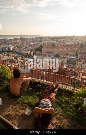Europe, Portugal, Lisbon. Two young people sitting in front of a panorama of the city of Lisbon at sunset.