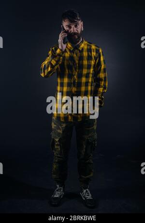 Fashion portrait on a black background of a bearded male model talking on his mobile phone - Stock Photo