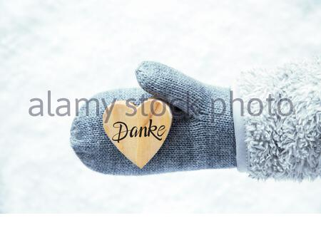 Heart With German Calligraphy Danke Means Thank You. Hand In A Glove With Fleece And Snow. - Stock Photo