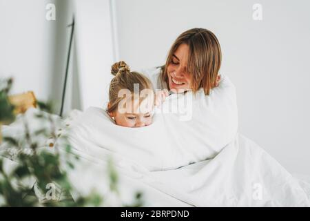 Cute toddler girl long fair hair big grey eyes looking at camera having fun with mother on bed stay at home - Stock Photo