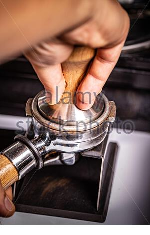 Barista presses ground coffee using tamper. - Stock Photo