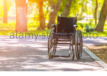 Empty wheelchair parked in park on road - Stock Photo