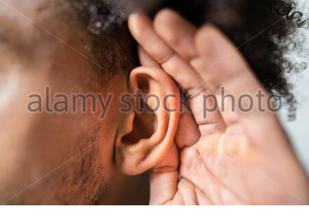 Person Trying To Hear With Hand Over Ear - Stock Photo