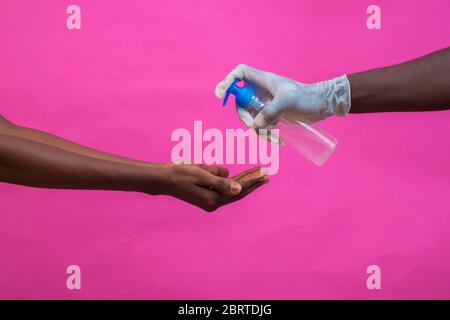 young black man's hand with a glove pouring a hand sanitizer on someone's hand - Stock Photo