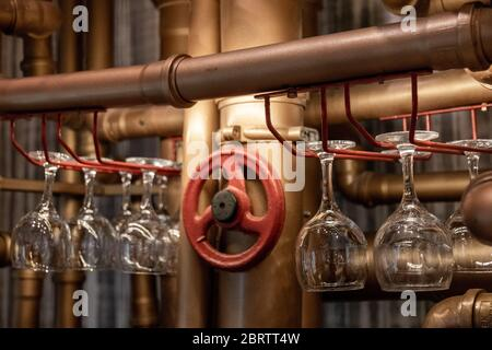 Shiny transparent empty wineglasses are hanging upside down on bar shelves made from water pipes painted in bronze and red colors. Drinking glasses di - Stock Photo