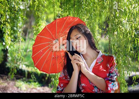 Beautiful oriental woman under willow tree - Stock Photo