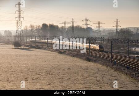 Virgin Trains class 390 Pendolino train under a mass of catenary and national grid pylons on the electrified west coast mainline - Stock Photo