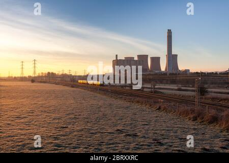 London Midland Siemens Desiro class 350 electric train passing the coal fired Rugeley power station on the electrified west coast mainline - Stock Photo