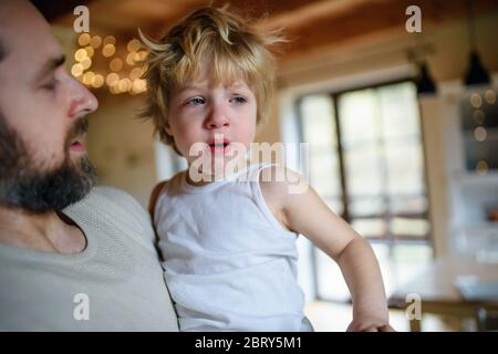 Father with small sick unhappy son indoors at home, comforting him. Stock Photo
