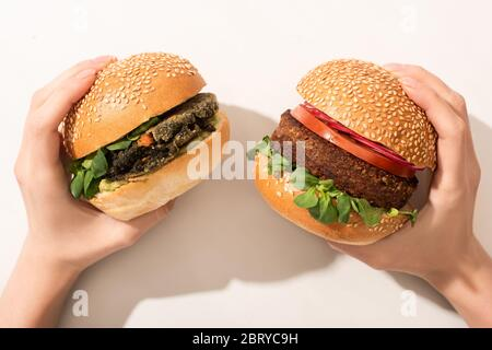 cropped view of woman holding delicious vegan burgers on white background - Stock Photo
