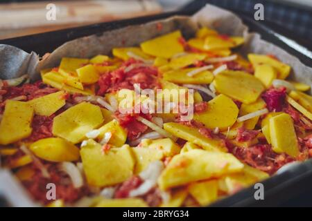 A simple recipe for food. Baked potatoes with red fish in the oven. Ready lunch on a close-up tray. - Stock Photo