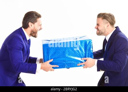 Two businessmen with aggressive expression pull box in opposite directions. Business rivalry concept. Men or businessmen with mad faces take away from each other package, isolated on white background. - Stock Photo